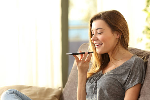 Girl using a smart phone voice recognition stock photo