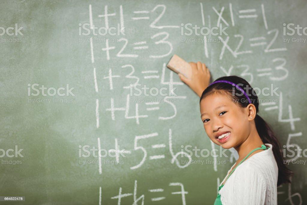 Girl using a sponge for blackboard royalty-free stock photo