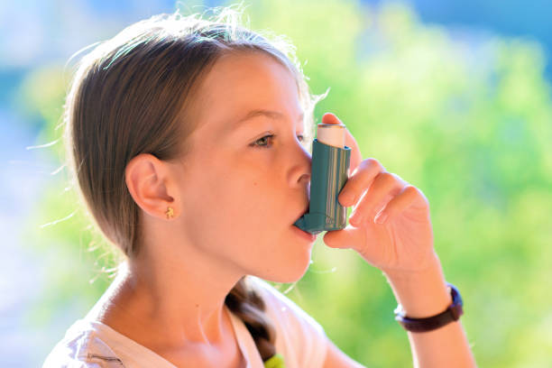Girl using asthma inhaler in a park stock photo