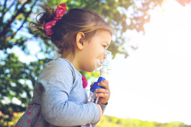 Girl using asthma inhaler in a park Cute girl making inhalation therapy by the mask of inhaler smoke inhalation stock pictures, royalty-free photos & images