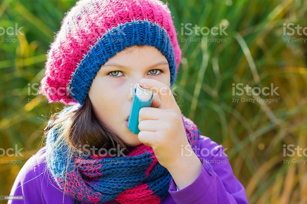 Girl Using Asthma Inhaler on an autumn day stock photo