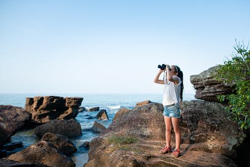 Girl using binoculars in the sea