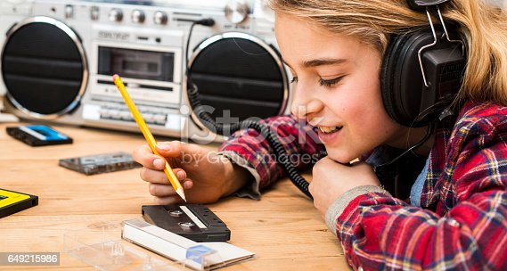 istock girl using cassette deck retro background 649215986