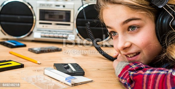 istock girl using cassette deck retro background 649246218