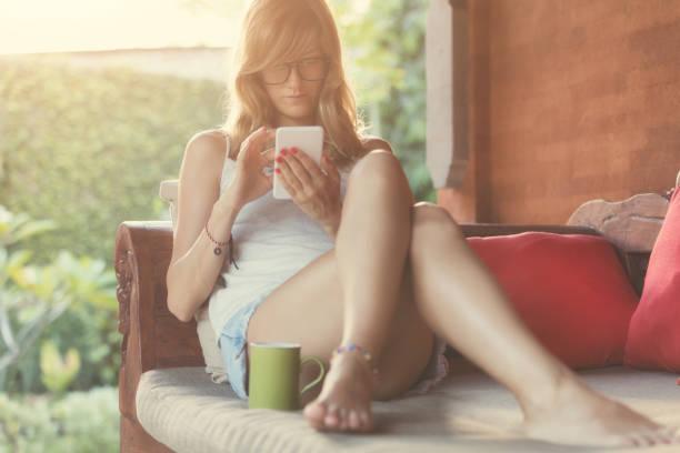 mädchen mit handy und trinken kaffee / tee auf der garten couch. - garden types stock-fotos und bilder