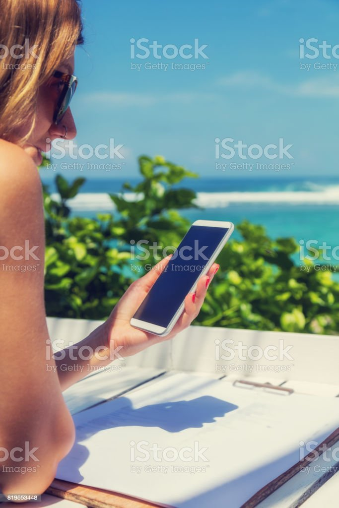 Girl using cellphone in the coffee shop on a tropical exotic beach. stock photo