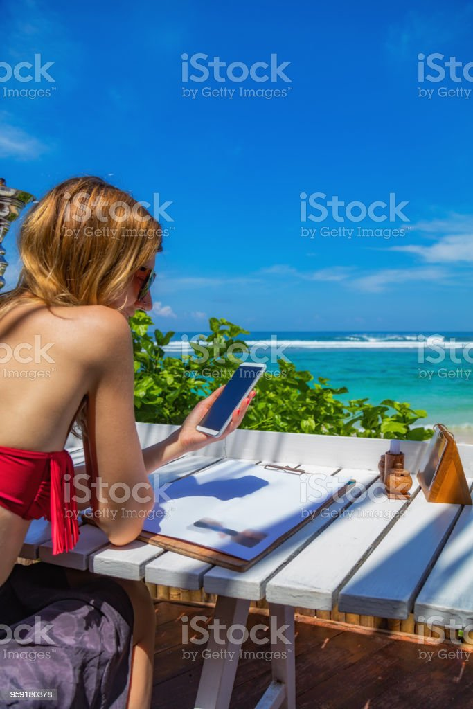 Girl using cellphone in the restaurant on a exotic tropical beach. stock photo