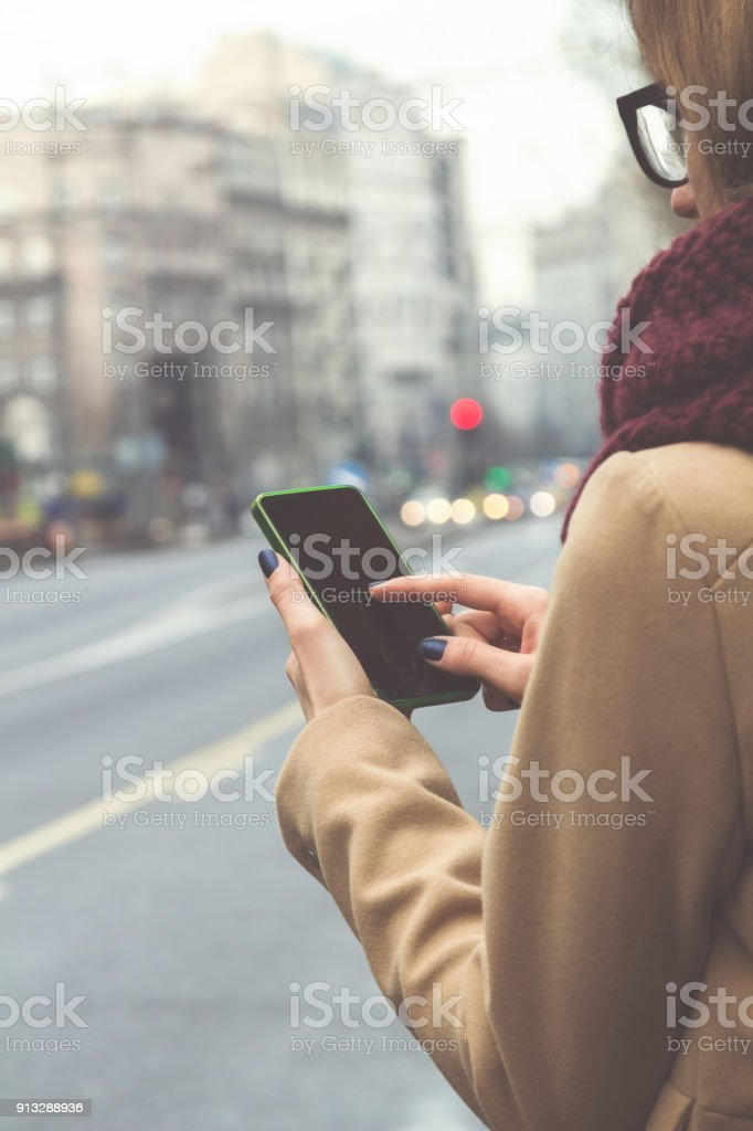 Girl using cellphone while crossing the big street. stock photo