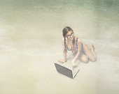 girl using computer on the beach