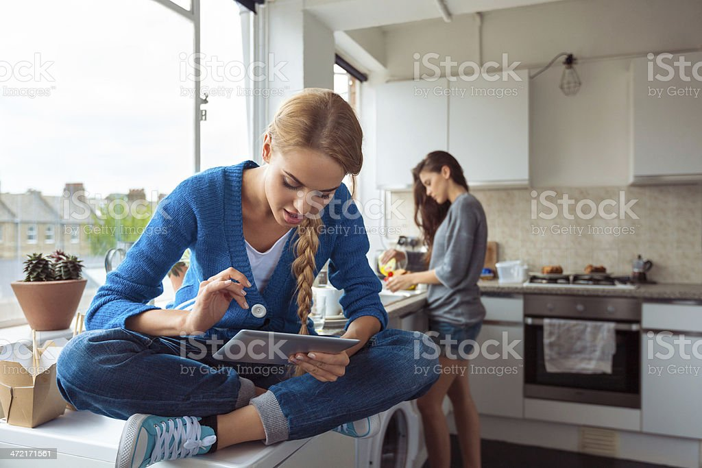Girl using digital tablet Roommates lifestyle. Young woman using a digital table while her friend washing dishes in the background. 20-24 Years Stock Photo
