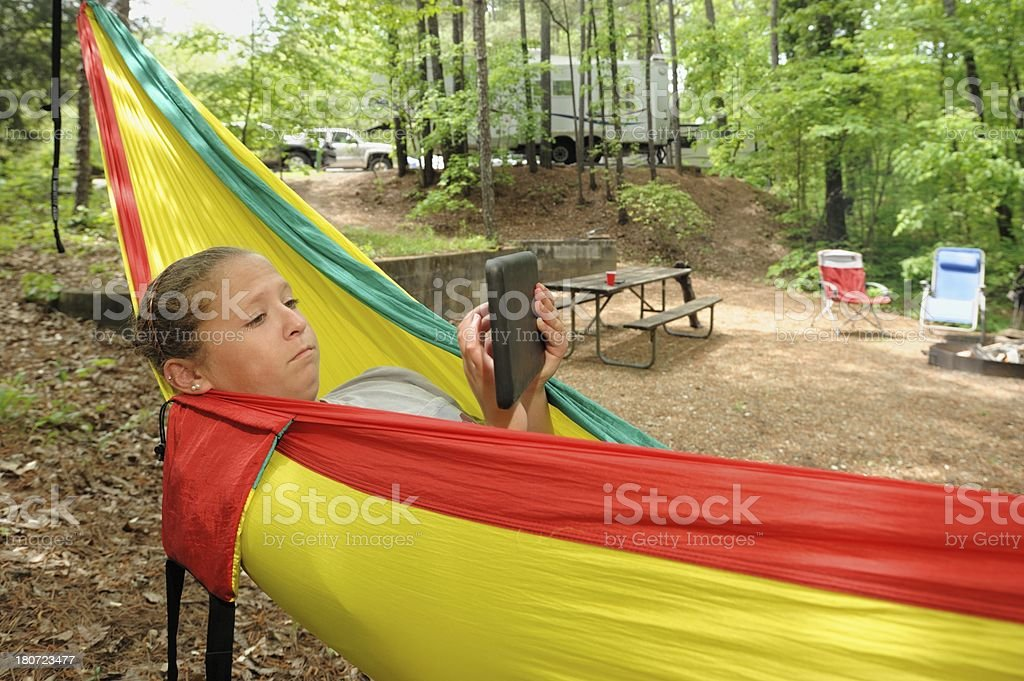 Girl using electronic tablet in hammock campground royalty-free stock photo