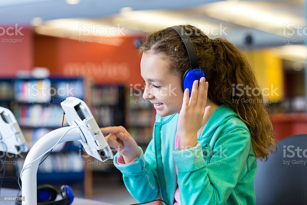 Girl using headphones and tablet to listen to library audiobook stock photo