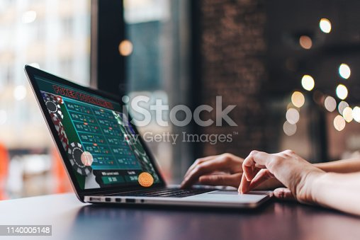 1032204252 istock photo Girl using her laptop for taking part in online poker tournament 1140005148