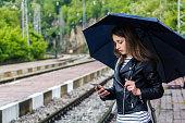 Beautiful Girl  using her phone on the railway station