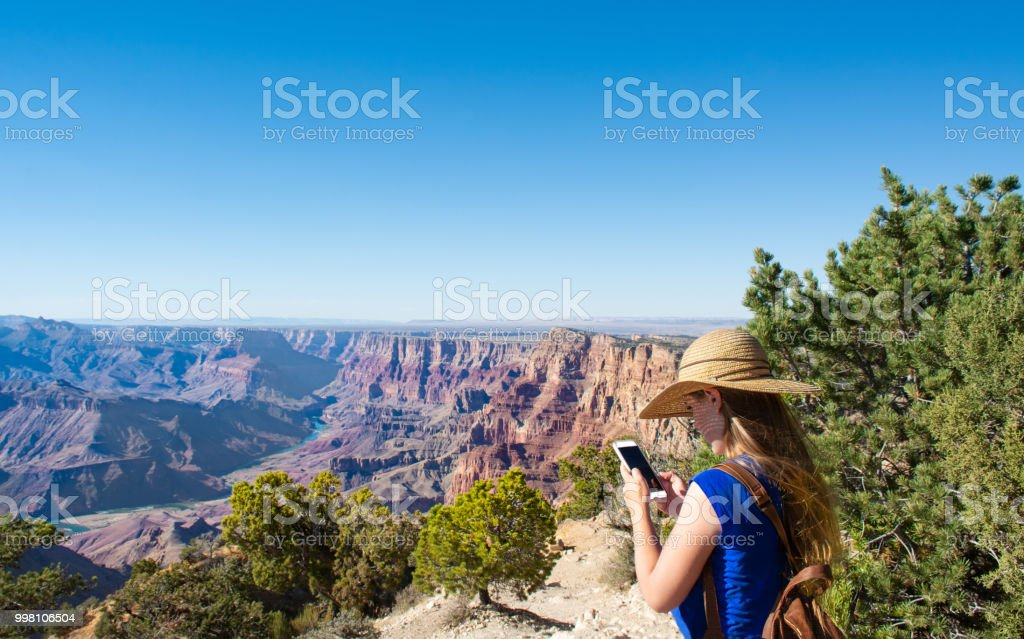 Girl using her phone, relaxing on top of mountain on a hiking trip. stock photo