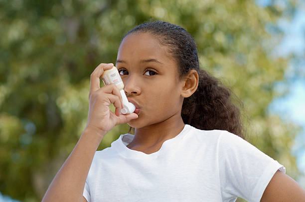 girl (7-9) using inhaler, outdoors - astmatisk bildbanksfoton och bilder