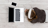 Top view header image of girl using laptop on floor with headset to stream music or movie
