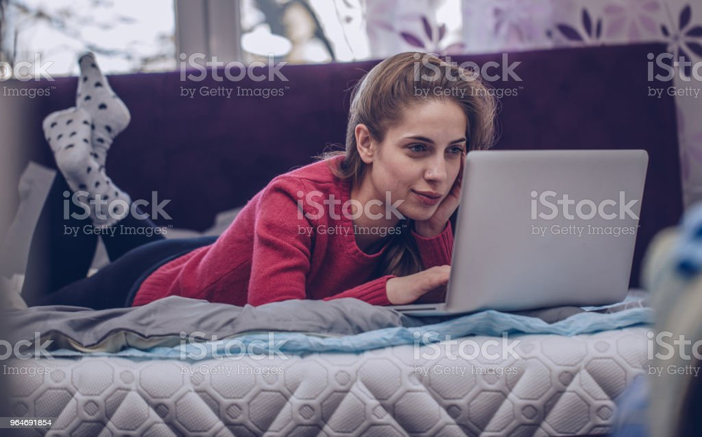 Girl using laptop in bed royalty-free stock photo