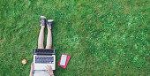 Girl using laptop in grass
