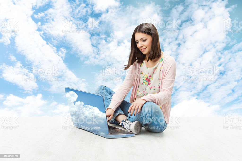 Girl using laptop over sky background, woman and notebook royalty-free stock photo