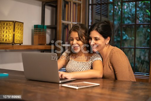 istock Girl using laptop with your mother at home 1079189990