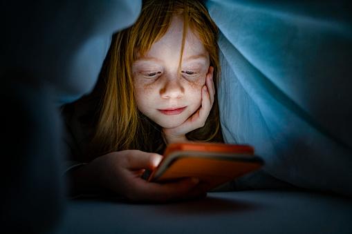 Girl using mobile phone in bed in the dark