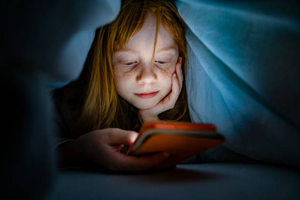 Girl using mobile phone in bed in the dark Girl using a mobile phone in the night. Kid skipping sleep hooked on the phone one girl only stock pictures, royalty-free photos & images