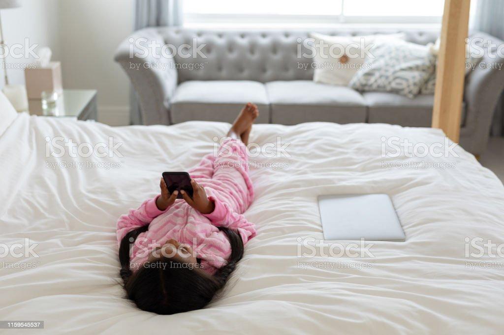 Astounding Girl Using Mobile Phone While Lying On Bed In Bedroom Stock Spiritservingveterans Wood Chair Design Ideas Spiritservingveteransorg