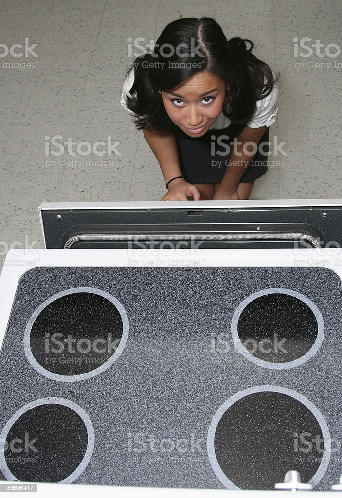Girl Using Oven royalty-free stock photo