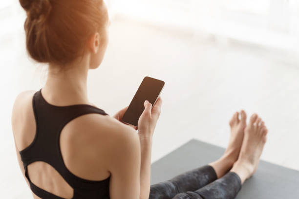 Girl using phone after practicing yoga on mat Girl using phone after practicing yoga on mat, having break after training yogi stock pictures, royalty-free photos & images
