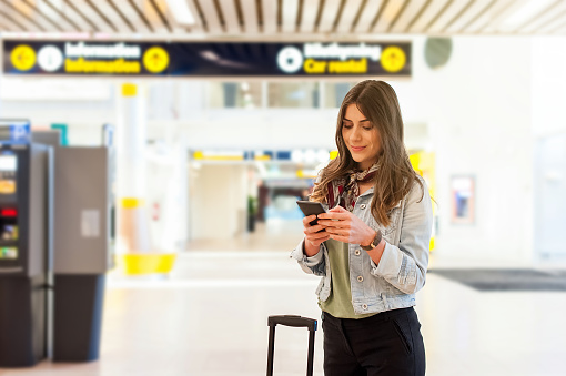 Young woman at the airport with trolley bag, talking on the phone