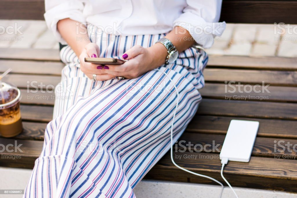 Girl using  phone while charging on the power bank stock photo
