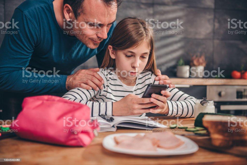 Girl using smart phone and doing homework at kitchen stock photo