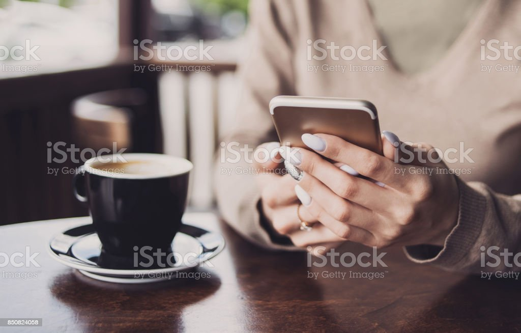 Girl using smart phone in coffee shop stock photo