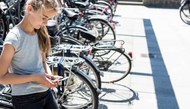 mädchen mit smartphone-header - fahrradhalter stock-fotos und bilder