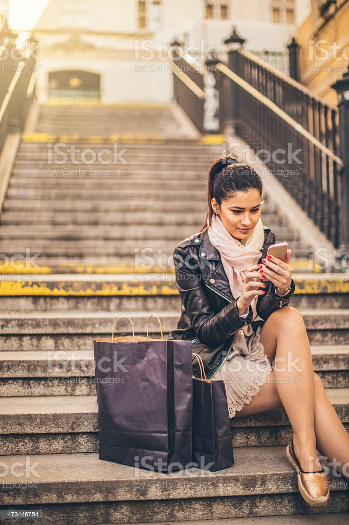 Girl using smartphone outdoors stock photo