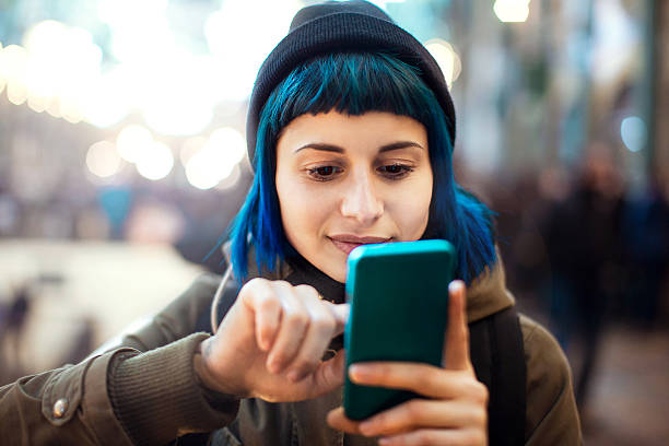 Girl using smartphone Girl with blue hair using smartphone student life stock pictures, royalty-free photos & images