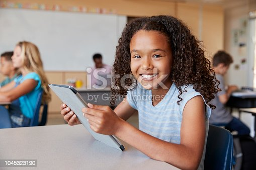 Girl using tablet in school class smiling to camera close up