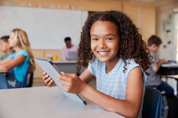 girl using tablet in school class smiling to camera close up - school building stock pictures, royalty-free photos & images