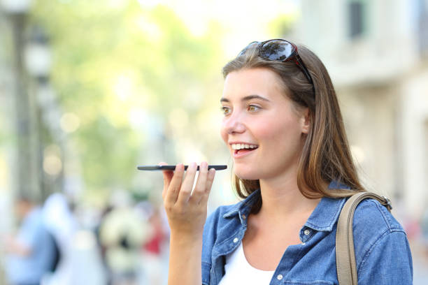 girl using voice recognition of the phone in the street - voce foto e immagini stock