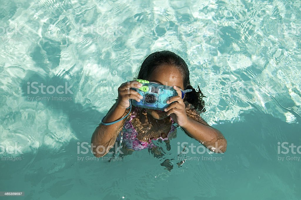 Girl Using Waterproof Camera in Swimming Pool stock photo
