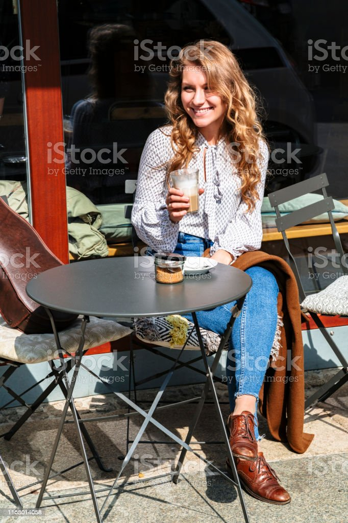 Beautiful young girl violinist sitting on coffee break in street cafe...