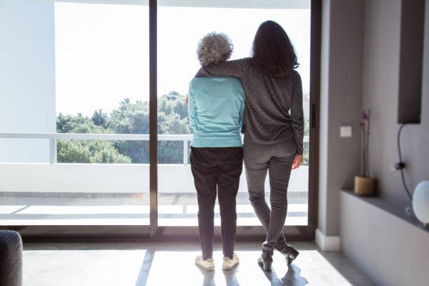 Girl visiting grandma Girl visiting grandma. Back view of young and elderly women standing and looking out window. Family and taking care concept aging stock pictures, royalty-free photos & images
