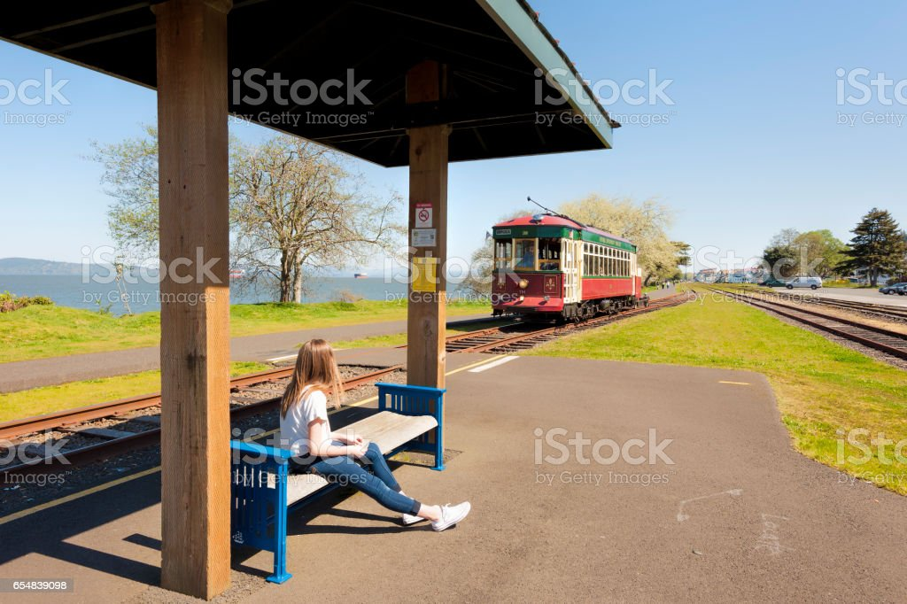 Girl waiting at trolley stop on Astoria Oregon Waterfront stock photo