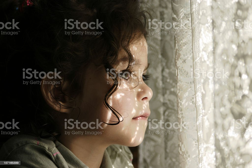 Girl Waiting Patiently at the Window stock photo
