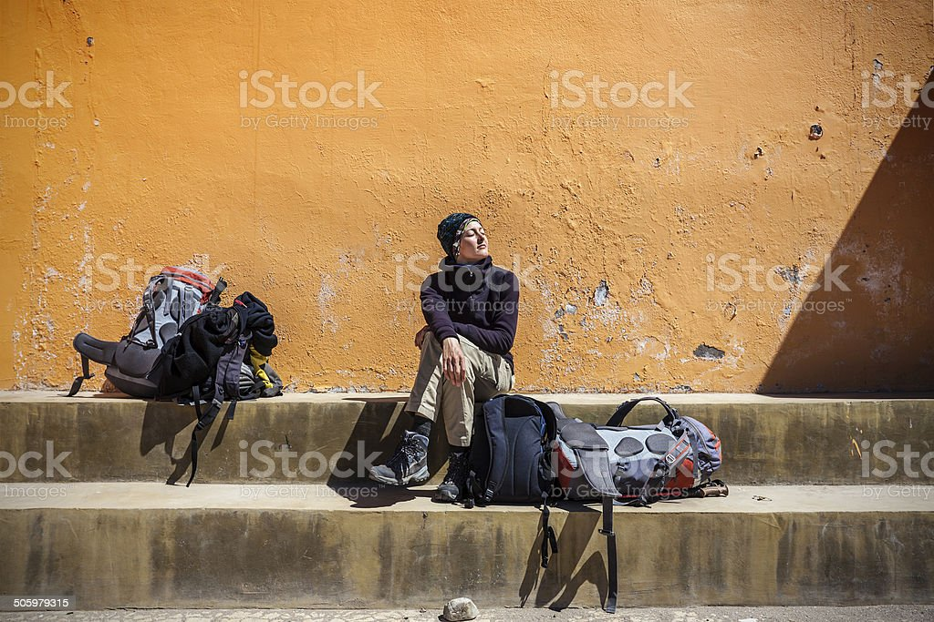 Girl waiting with backpacks in sun. stock photo