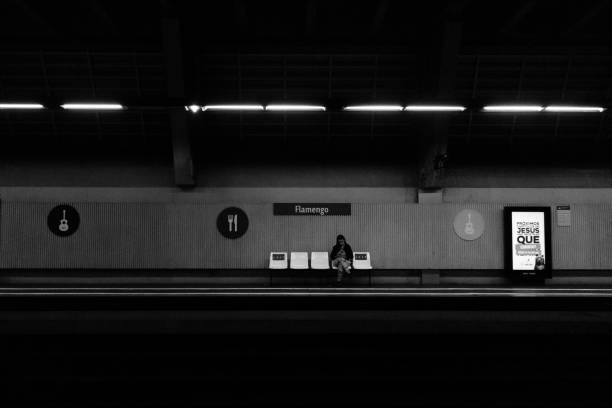 Girl waits for the subway at Flamengo station while checking her smartphone. Image process contain exessive noise or grain. Black and white image stock photo