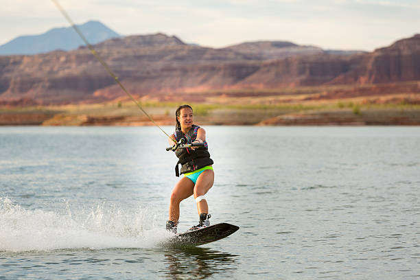 Girl Wakeboarding in Desert Sunshine Girl wake boarding at Lake Powell, Utah in the summer sunshine. lake powell stock pictures, royalty-free photos & images