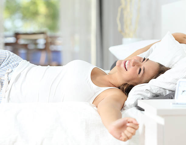 Girl waking up stretching arms on the bed stock photo