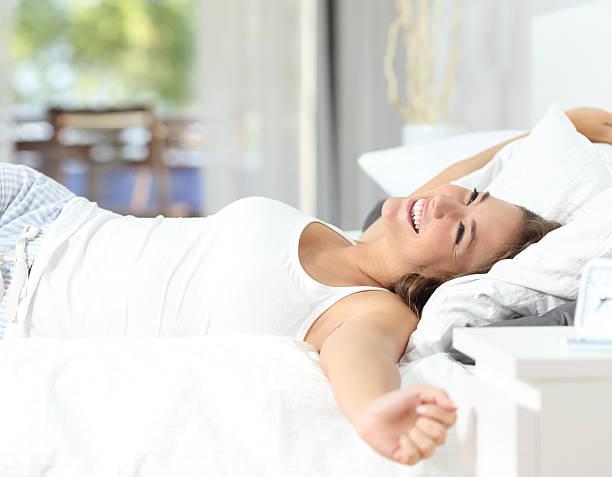 Garota acordar Alongando os braços sobre a cama - foto de acervo